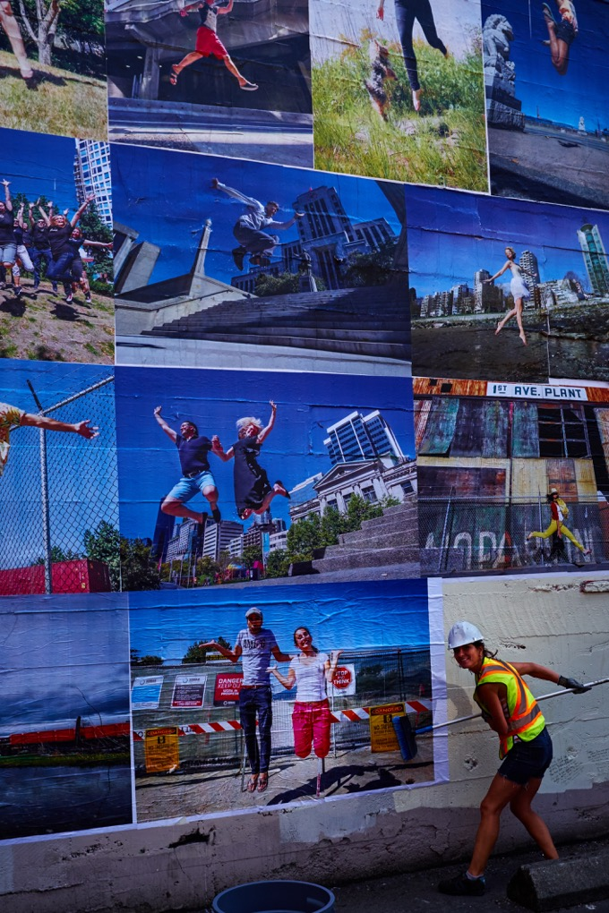 Photos of Eyoalha putting up posters on wall of joy by Gregory Mullaly