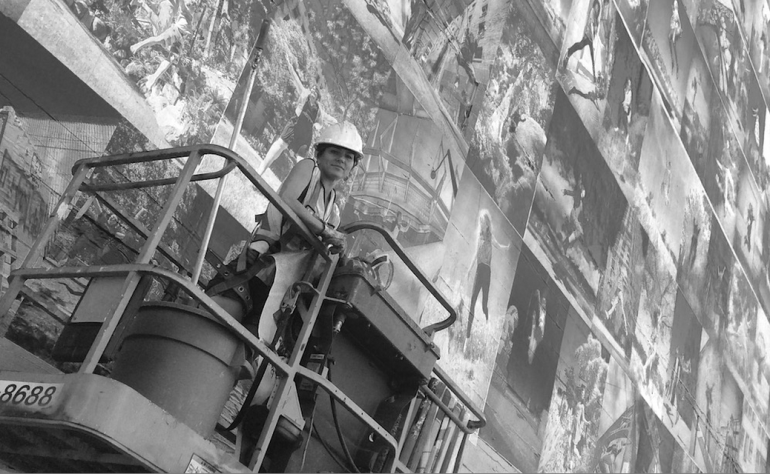 Photo of Eyoalha Baker working on the Wall of Joy Mural by Alexandre Legere